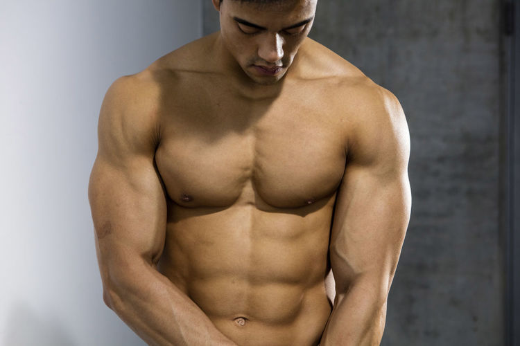 Muscular male fitness model posing behind a grey wall with his gaze directed downwards. Adult Asian  Athlete Body & Fitness Human Body Man Nam Vo Shirtless Sportsman Abdomen Fitness Model Grey Wall Handsome Head Down Hunk Male Masculinity Muscle Muscular Build One Person Shirtless Strong Studio Shot The Human Body Torso