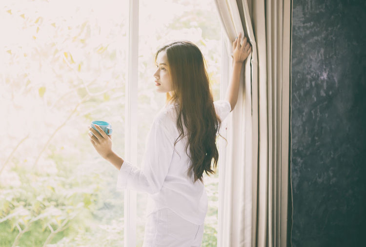 Adult Casual Clothing Contemplation Curtain Glass - Material Hair Hairstyle Holding Indoors  Leisure Activity Lifestyles Long Hair Looking One Person Real People Side View Standing Waist Up Window Young Adult
