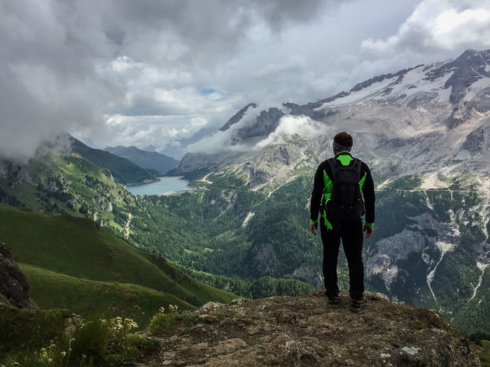 Full length rear view of hiker looking at mountains against cloudy sky from peak