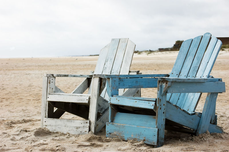 Old empty wooden chairs at beach