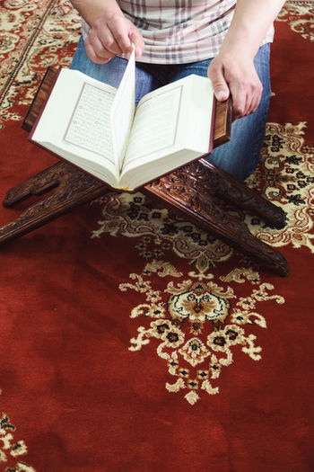 Man reading islamic holy book reading ayat of man dua reading koran at mosque. Activity Adult Art And Craft Book Floral Pattern Hand High Angle View Holding Human Body Part Human Hand Indoors  Leisure Activity Lifestyles Making Midsection One Person Pattern Publication Real People Women