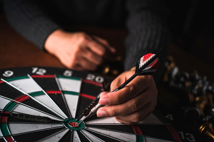 Midsection of person holding dart on dartboard