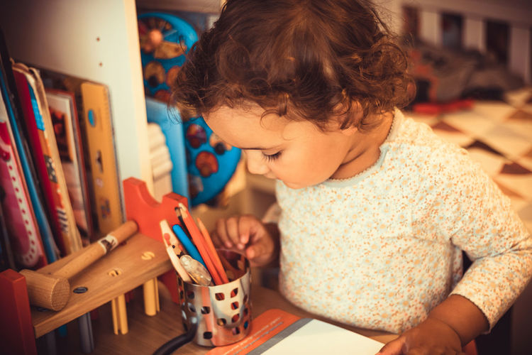 Little girl choosing crayons while coloring at home.