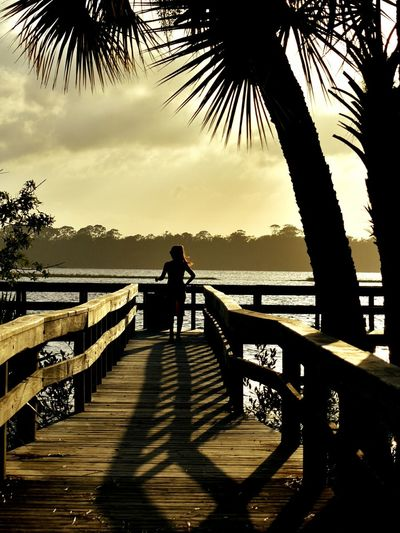 Silhouette man standing on pier over lake