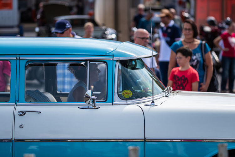 Lohmar, Germany - August 12, 2018: Visitors and historic US cars populate a huge parking lot - for editorial use only Mode Of Transportation Transportation Car Land Vehicle Motor Vehicle Incidental People Focus On Foreground City Day Real People Group Of People Outdoors Street Men People Travel Selective Focus Public Transportation Close-up Blue