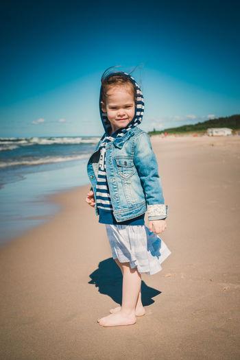 Full length portrait of cute girl standing at beach