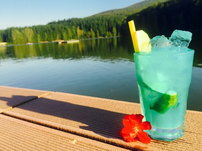 Close-up of drink on table by lake
