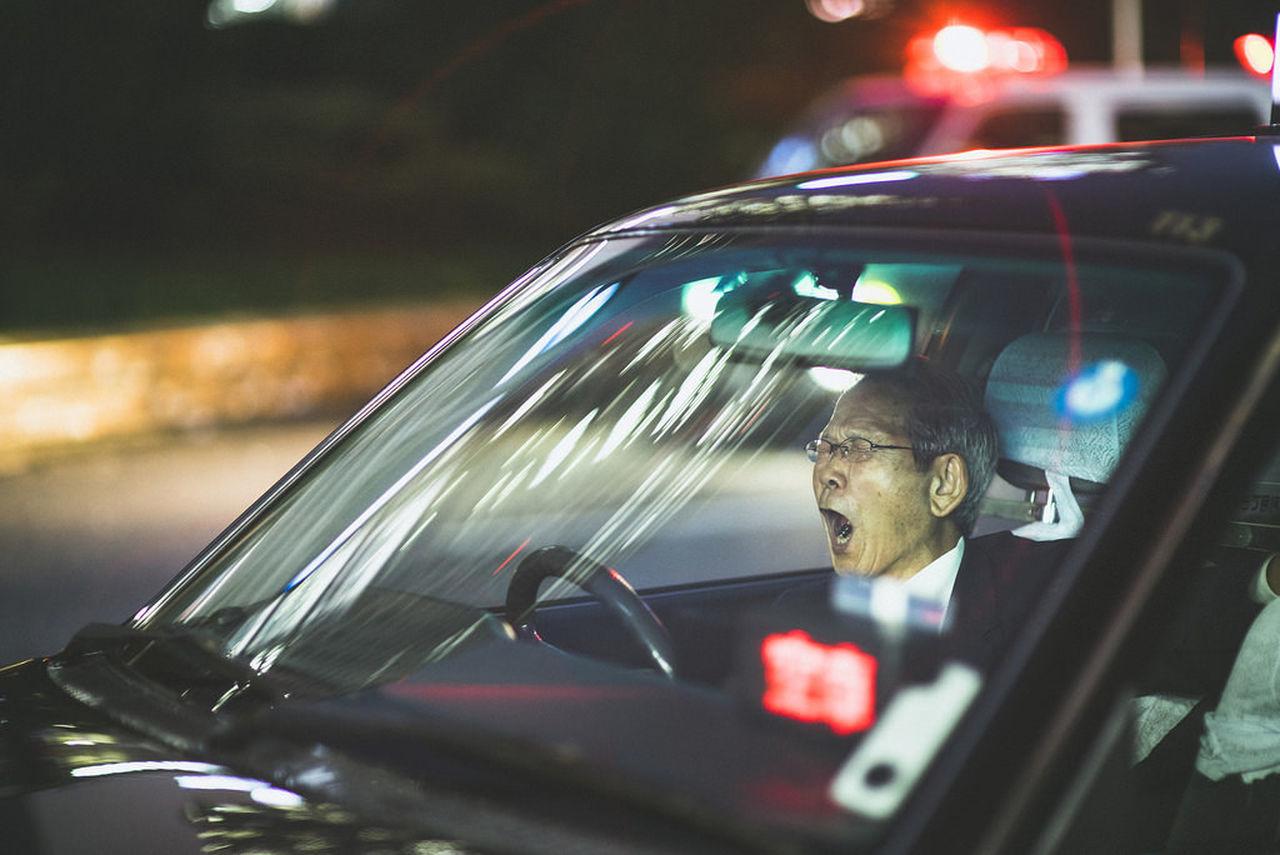 PORTRAIT OF MAN SEEN THROUGH CAR WINDSHIELD