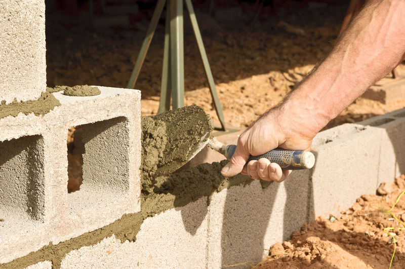 Cropped hands of man laying bricks at construction site