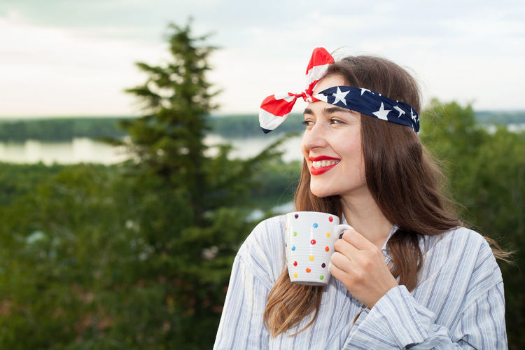 Smiling Woman Holding Coffee Cup While Looking At View In Forest