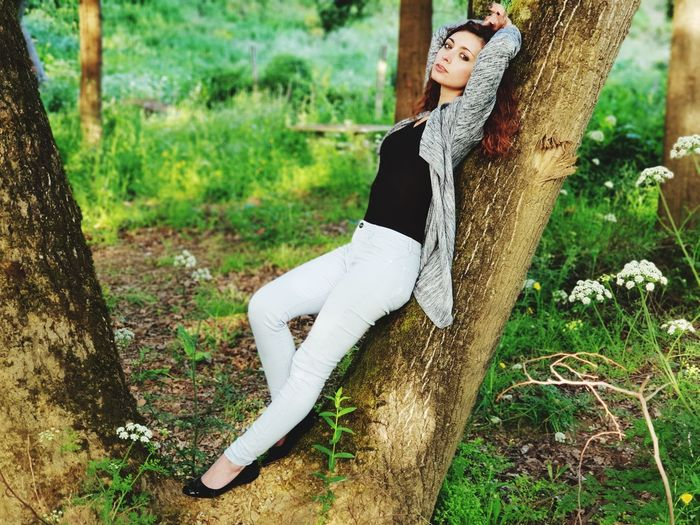 Side view portrait of woman leaning on tree trunk in forest