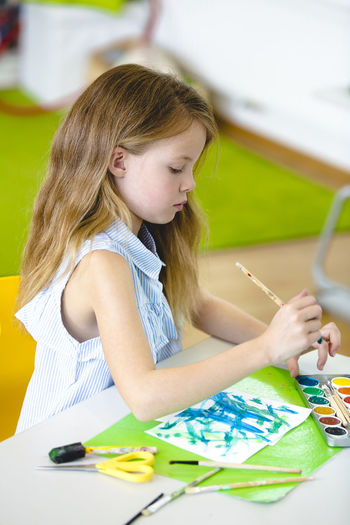 Girl Painting On Paper At Table