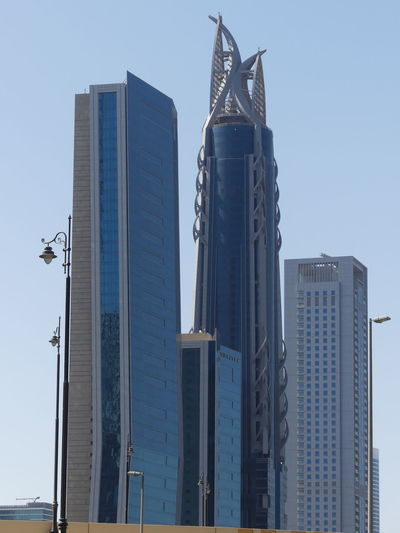 Skyscrapers on Sheik Zayed Road, Dubai, United Arab Emirates 2019 Dubai UAE 2019 Sheik Zayed Road Blue Sky Sunlight And Shade Low Angle View City No People Tall - High High Skyscrapers Towers Tower Blocks Modern Architecture Modern Design Steel And Glass Structures Streetlamps Full Frame Composition Outdoor Photography Modern Architecture Unusual Shape Building Exteriors