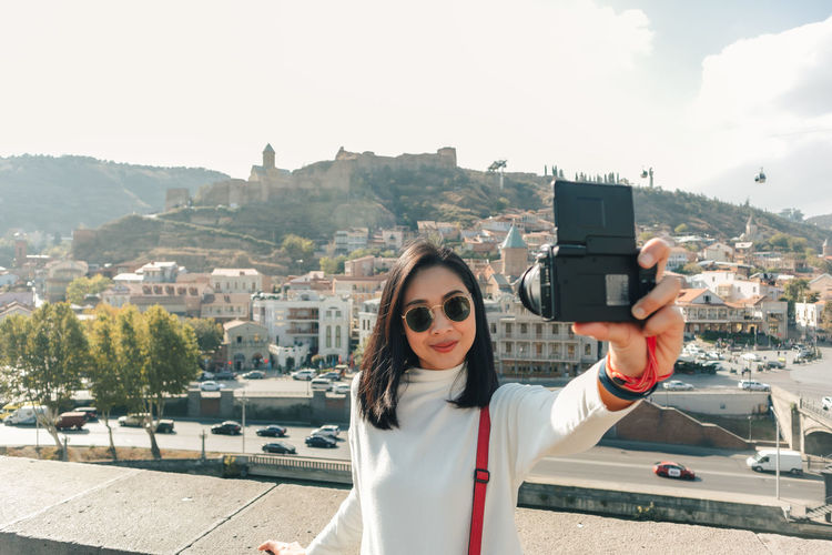 Portrait of young woman photographing cityscape against sky