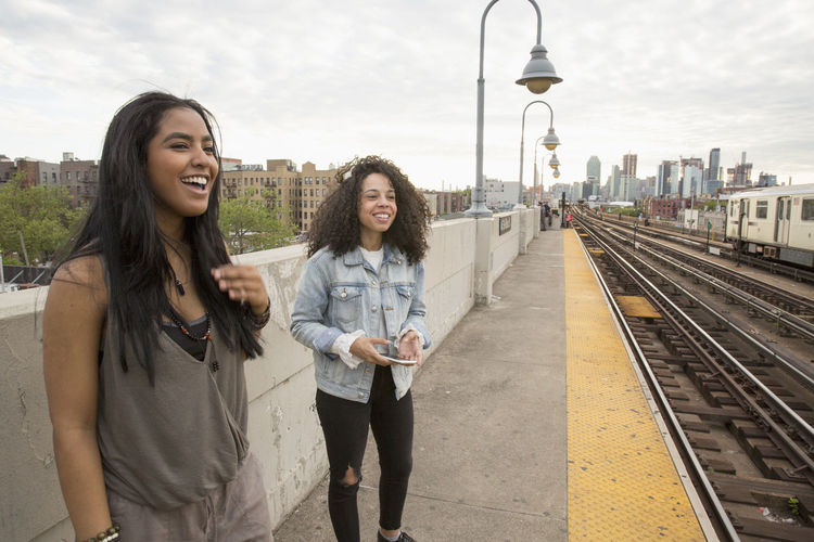 Happy young woman standing on railroad tracks in city
