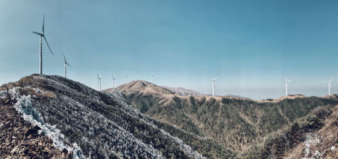 Panoramic view of wind turbines on landscape against sky