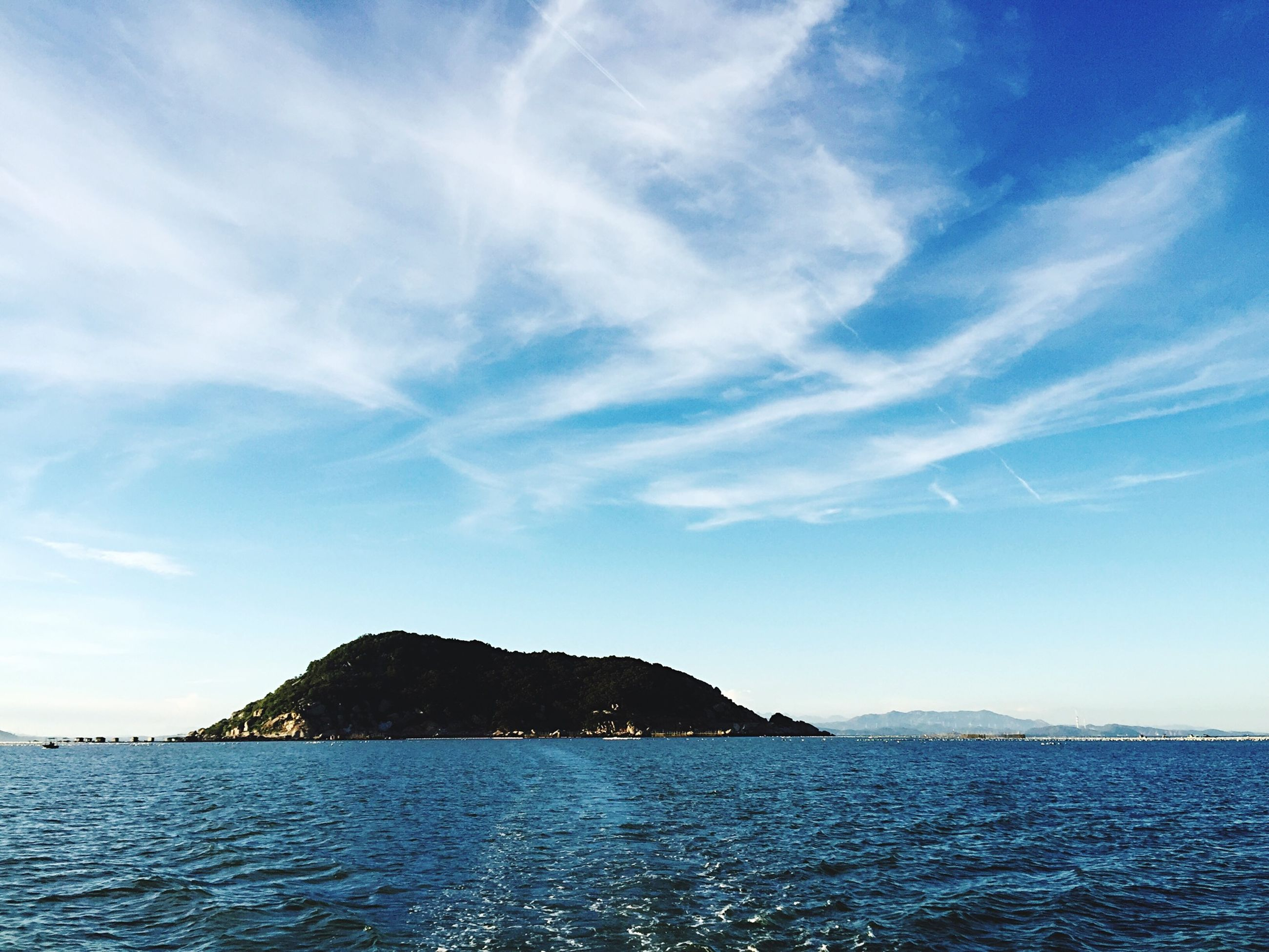sea, water, scenics, tranquil scene, waterfront, tranquility, sky, mountain, beauty in nature, nature, blue, rippled, idyllic, cloud, cloud - sky, mountain range, rock formation, non-urban scene, day, remote