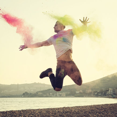 Portrait at sunset of a beautiful young man jumping with energy and colored powder. Colors Jump Man Adult Backlit Color Vibe Day Energetic Full Length Happiness Jumping Jumping For Joy Leisure Activity Men Mid-air Motion Nature One Man Only One Person Outdoors People Real People Sky Water First Eyeem Photo My Best Photo