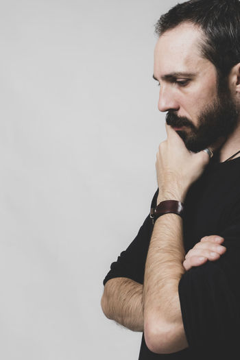 bearded thoughtful man on gray background Contemplation Standing Young Men White Background Young Adult Facial Hair Beard Indoors  One Person Studio Shot Indoors  Copy Space Men Mid Adult Men Looking Hand Males  Mid Adult Wall - Building Feature
