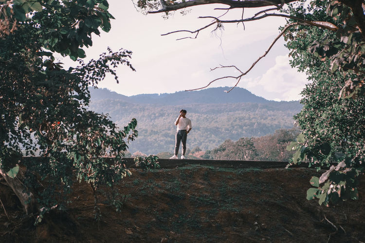 Man standing by tree on mountain against sky