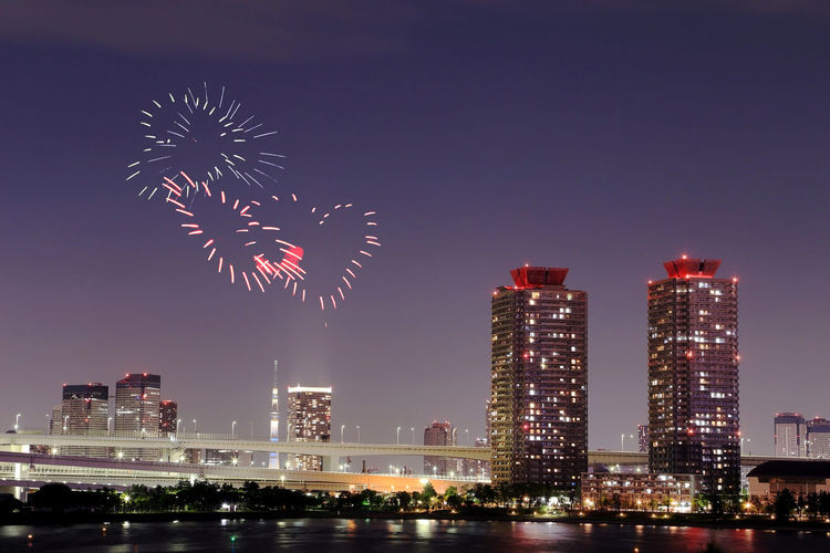 Firework display over illuminated buildings against sky at night