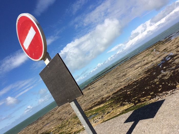 Tilt image of no entry sign at sea shore against sky