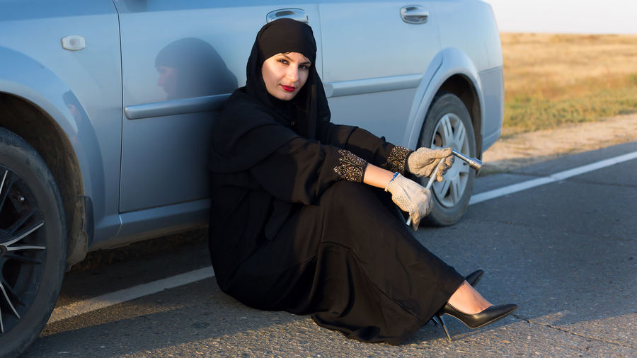 Full length of woman in burka sitting by car on road