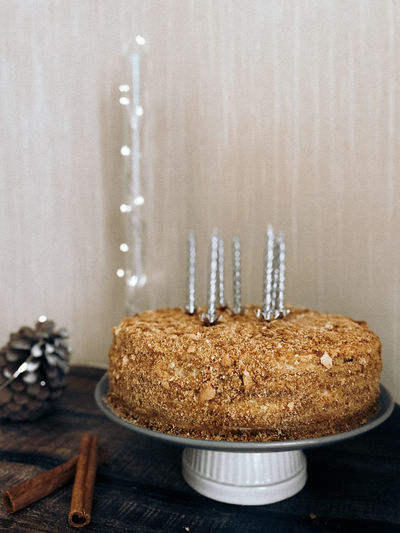 Close-up of cake on table against wall