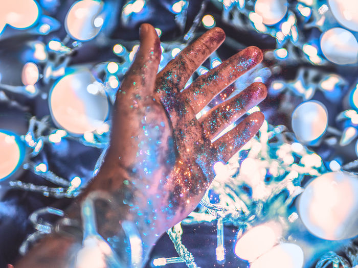 Human Hand Indoors  Selective Focus Close-up Illuminated Celebration Hand Real People Decoration Shiny Leisure Activity Lifestyles Focus On Foreground Human Body Part Finger Human Finger Multi Colored Night People Humanity Meets Technology