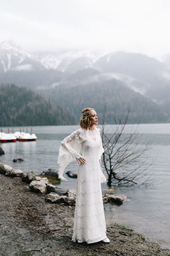 A beautiful young woman bride in a wedding lace dress stands in the middle of a lake and mountains