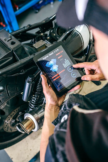 Mature mechanic using digital tablet by motorcycle in garage