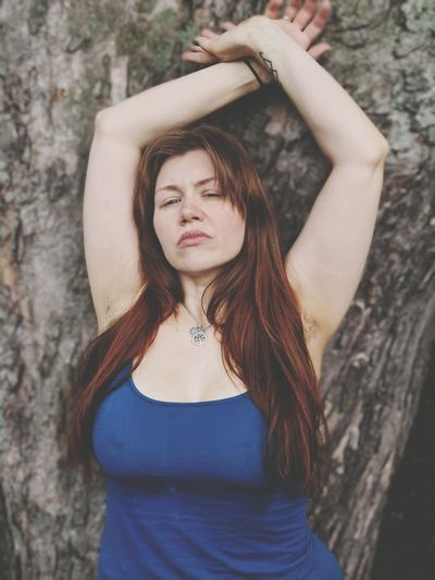 Beautiful young woman standing by tree trunk