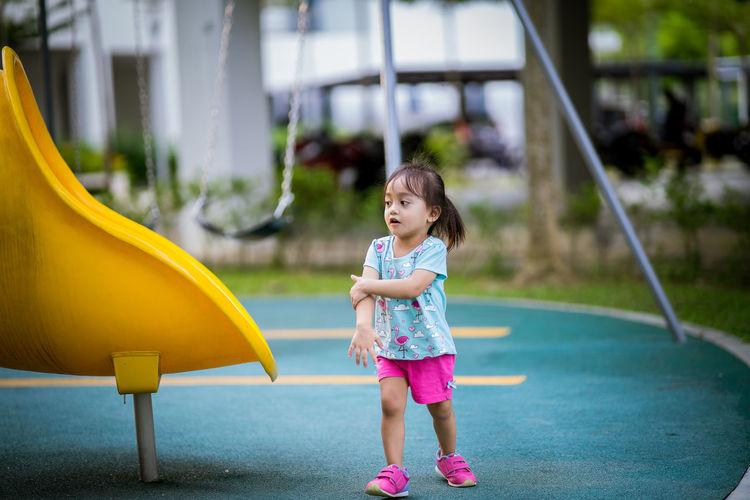 Full length of girl standing by slide