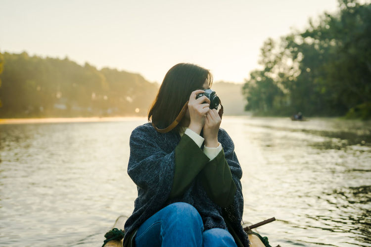 Solo asian woman take photo and travel by thai local bamboo boat in tropical forest and lake