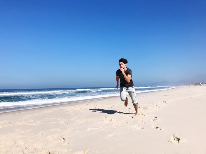 Full length of young man on beach against clear blue sky