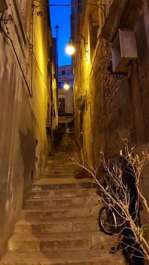 Narrow alley amidst illuminated street and buildings at night