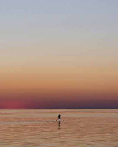 Silhouette person on the sup board on sea against sky during sunset.