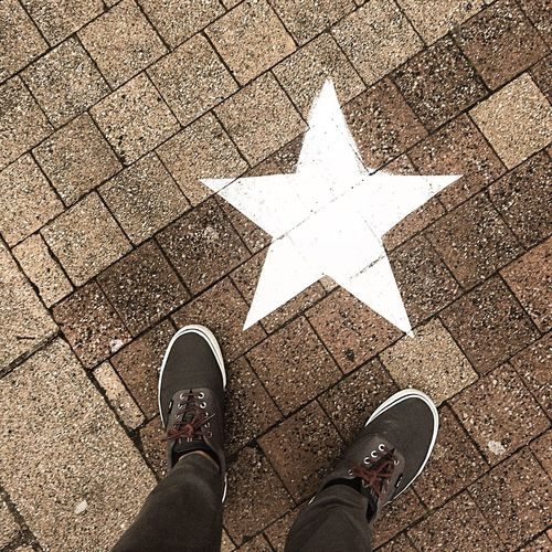 Low Section Of Man Standing By Star Shape On Footpath