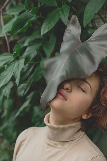 A beautiful plus size girl with red hair among the lush green branches of tropical plants.