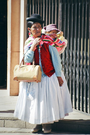 Bolivia Bowler Hat Carrying Child Casual Clothing Day Feel The Journey Front View Full Length Handbag  Hat Leaning Leisure Activity Lifestyles Looking Away Pollera Portrait Standing Travel Photography Waiting Woman