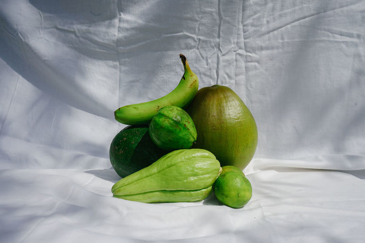High angle view of green fruits on bed