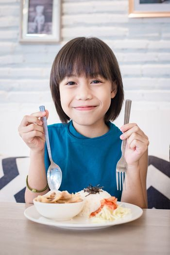Portrait of smiling girl having food at home