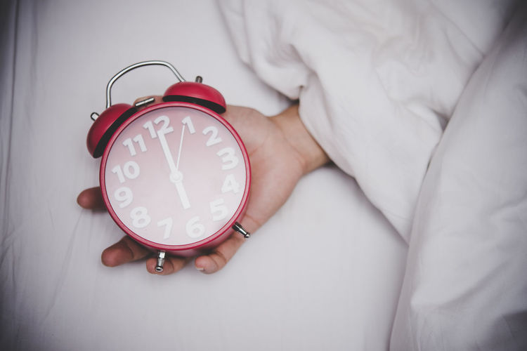 Cropped hand holding alarm clock on bed