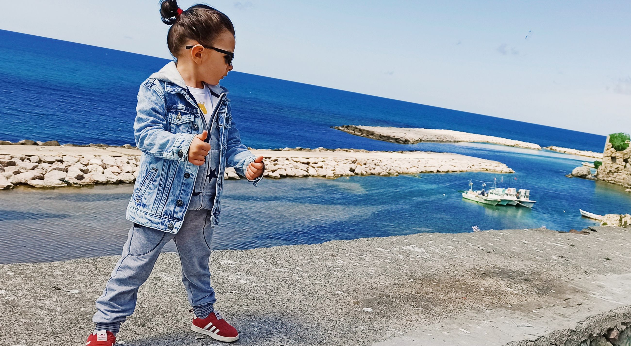 water, one person, sea, blue, beach, casual clothing, full length, standing, child, vacation, childhood, nature, day, leisure activity, sky, land, men, lifestyles, sunlight, glasses, outdoors, looking, beauty in nature, coast, sunny, horizon over water, scenics - nature, person, sunglasses