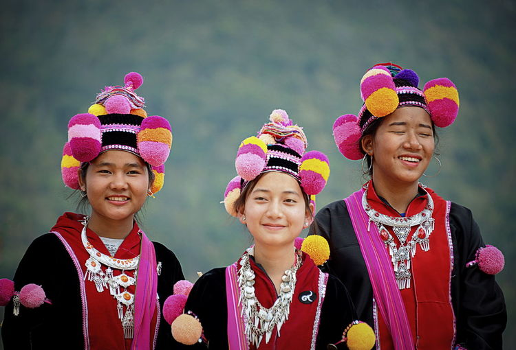 Portrait of smiling women in traditional clothing while standing outdoors