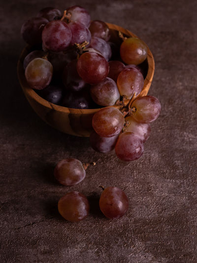 High angle view of grapes in basket on table