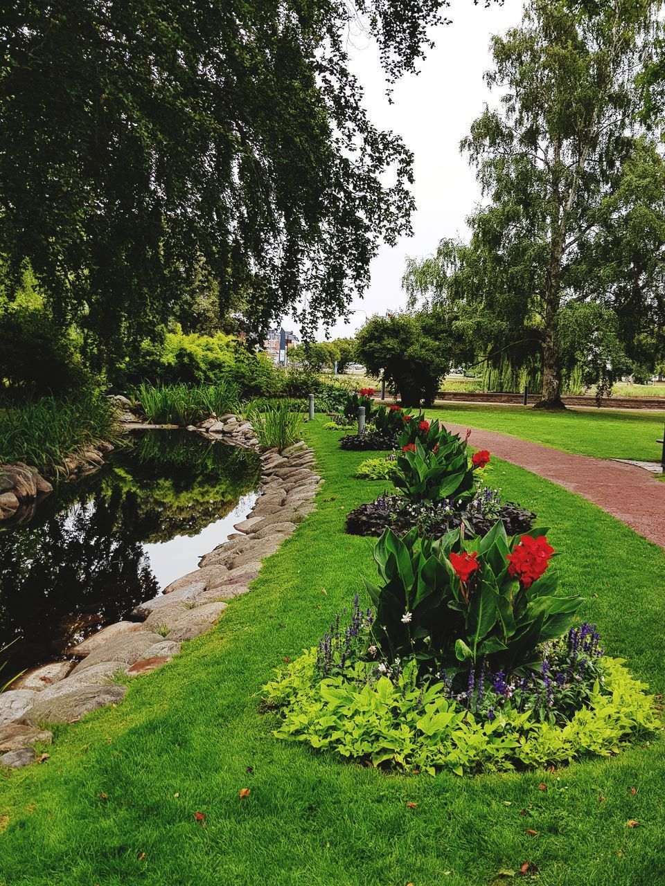 SCENIC VIEW OF FLOWERING PLANTS BY PARK IN GARDEN
