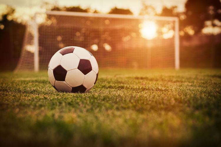 Close-up of soccer ball on field at sunset