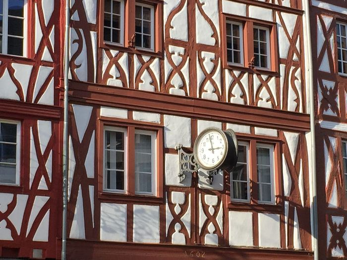 Low angle view of clock on glass window of building