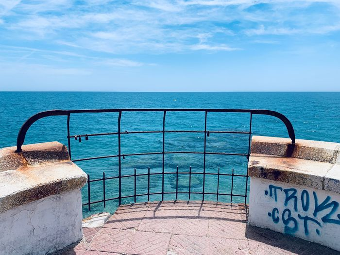 Railing by swimming pool against sea against sky